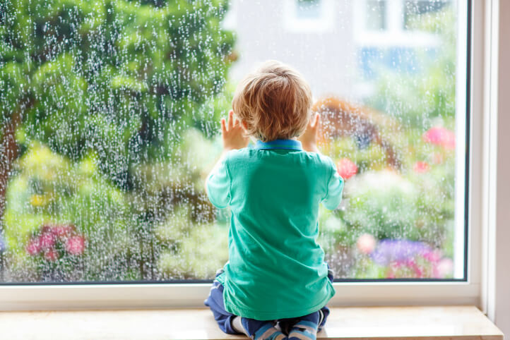 child looking outside window rainy day